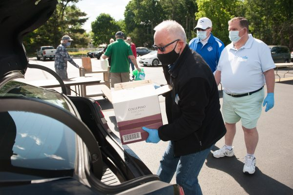 Volunteer unloads donated goods from van.