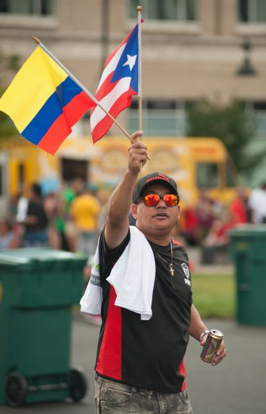 A man waves Colombian and Puerto Rican flags