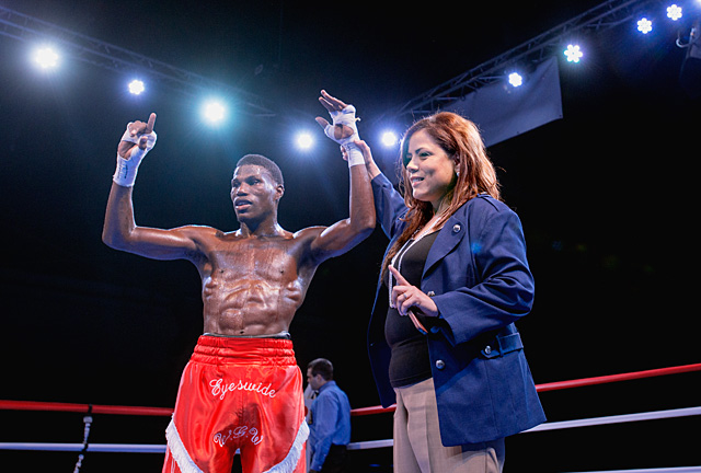 Boxing promoter Mercedes Vazquez-Simmons raises the hand of a winning boxer during the Throwdown at the Armory II put on by Pretty Girl Productions Aug. 23 at the Main Street Armory in Rochester.