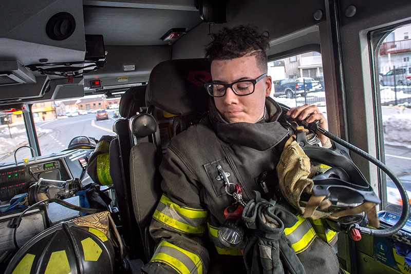 Rochester Fireman Jonathan Quinones of the Engine 5 Firehouse straps on his oxygen tank while en route to a call on Lake Ave in Rochester March 8.