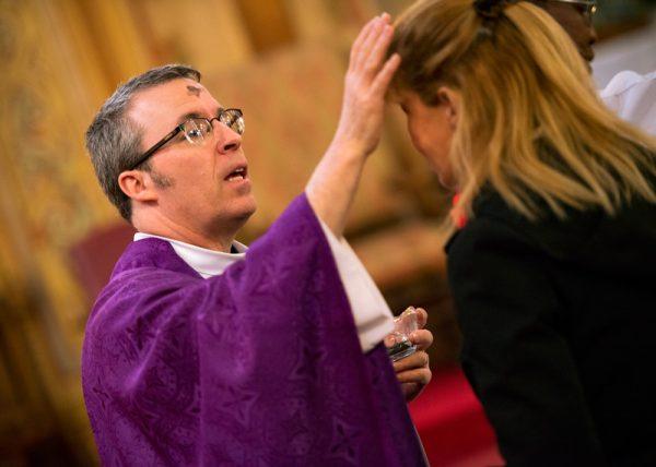 A priest rub ash on womans forhead