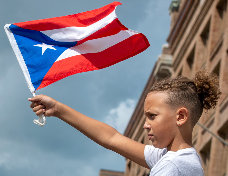 Boy waves a Puerto Rican flag.