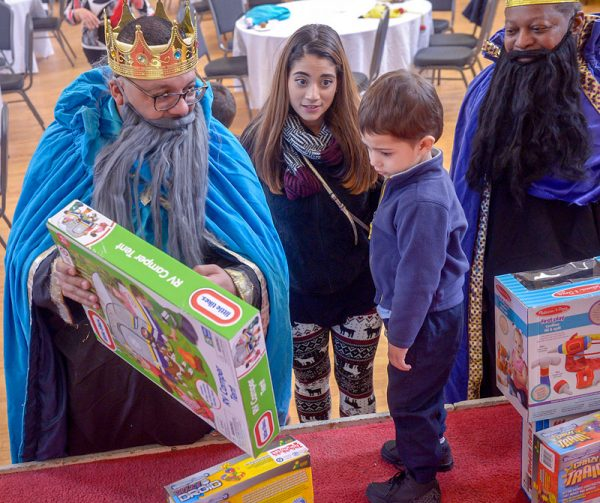 A man dressed as a king presents a child with a gift.