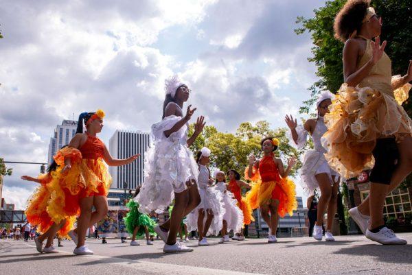 Dancers walk in a parade.