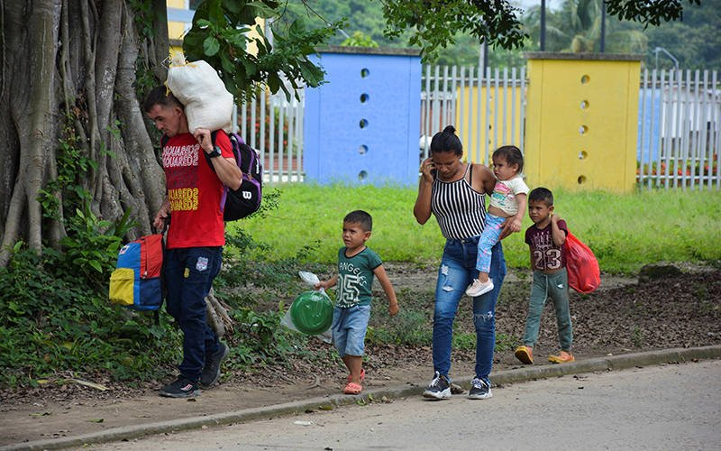 Venezuelan refugees walk down a street in Arauquita, Colombia, April 5, 2021, after fleeing their country due to a military offensive. Church groups in Colombia are mobilizing to support thousands of Venezuelan refugees who recently fled the military offensive and are now stuck in the remote Colombian border town. (CNS photo by Reuters)
