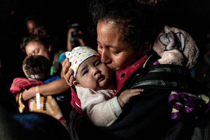 A mother from Guatemala seeking asylum in the U.S. kisses her 3-month-old baby while waiting to be escorted by Border Patrol agents in Roma, Texas, April 7, 2021, after crossing the Rio Grande into the United States. (CNS photo by Go Nakamura/Reuters)
