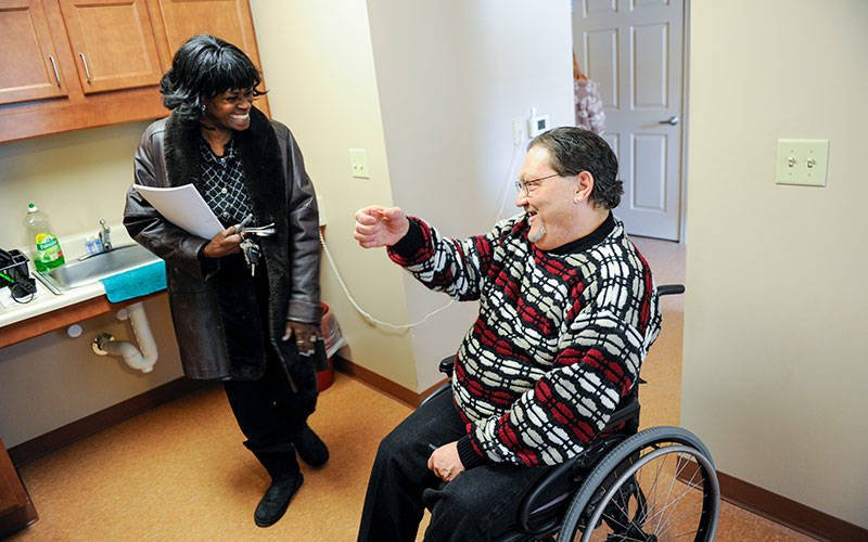 A man sitting in a wheelchair gives a tour of his apartment to a woman who is wearing a coat and holding keys and papers.