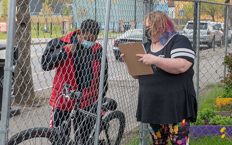 A woman and man speak to each other from opposite sides of a chain-link fence. The man is standing next to a bicycle, and the woman is holding a clipboard.