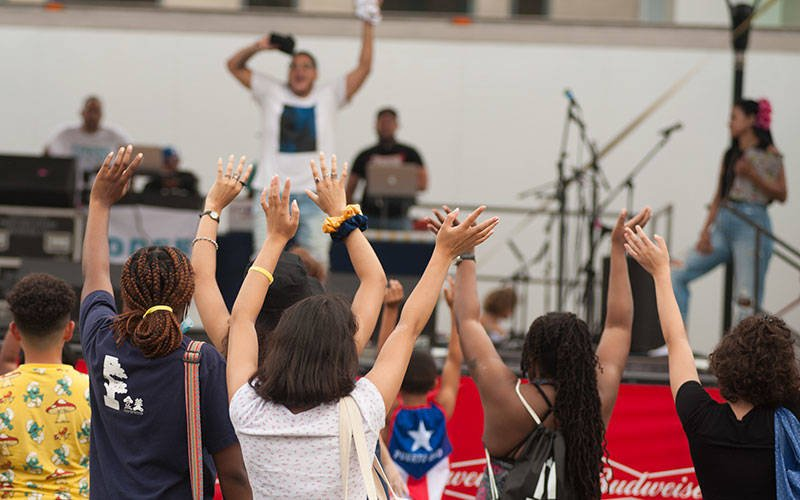 People gathered at Parcel 5 in Rochester Aug. 21 to celebrate the 51st-annual Puerto Rican Festival. People raise their hands as they face a stage filled with musicians and musical instruments.