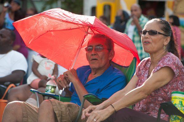 A older man sits underneath a red umbrella.