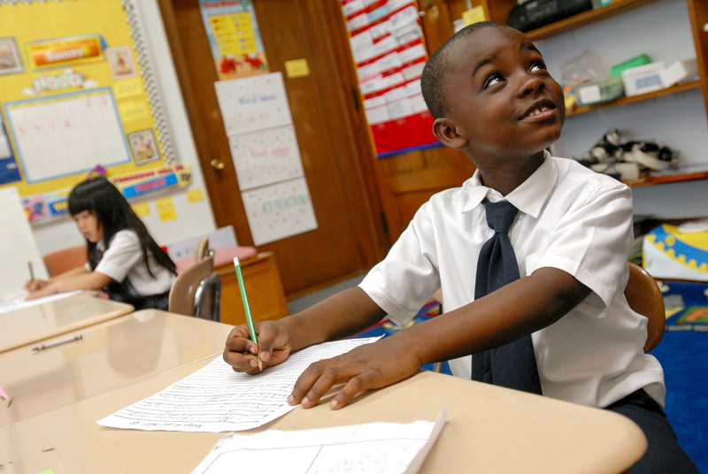 Umenzi Thompson (foreground) and Samantha Manioci (rear), students at Nazareth Hall Elementary School in Rochester, N.Y., work at their desks June 7, 2007. (photo by Mike Crupi)