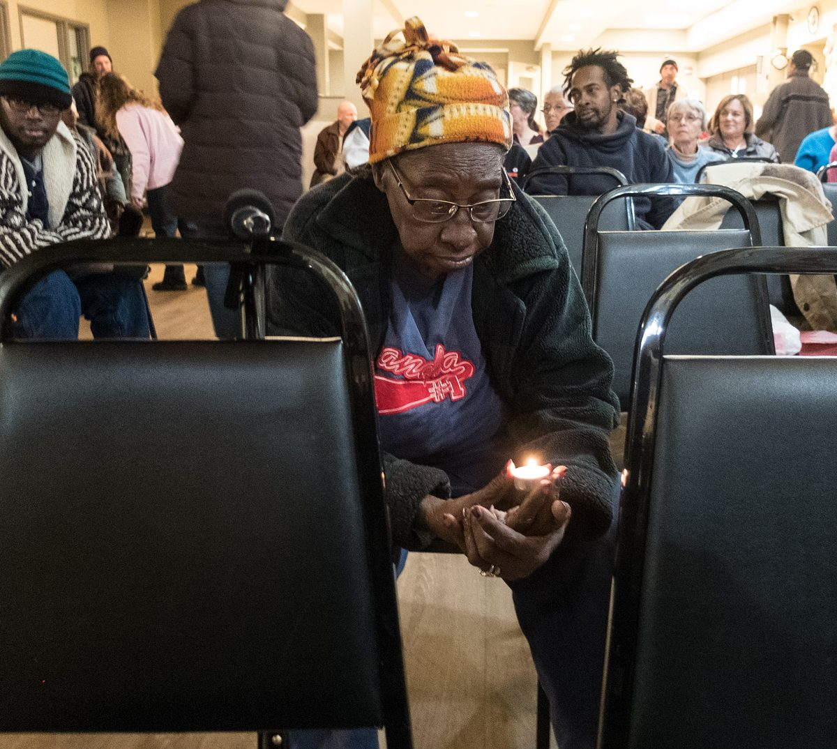 Betty Hall prays while holding a candle during the Interfaith Prayer Service for an End to Poverty at the House of Mercy on Nov. 15. The service is part of a weeklong events leading up to the Day of the Poor. Courier Photo by John Haeger.