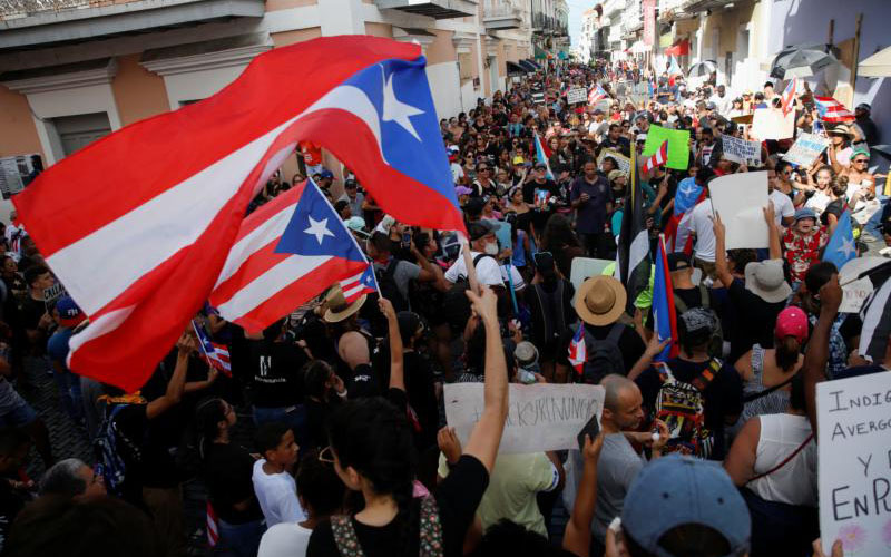 People chant slogans as they wave Puerto Rican flags during ongoing protests calling for the resignation of Gov. Ricardo Rossello in San Juan July 20, 2019. Rossello said July 21 that he will not resign in the face of public furor over an obscenity-laced online chat deriding gays, women and others that was leaked. He said he will not seek reelection or continue as head of his pro-statehood political party. (CNS photo/Marco Bello, Reuters)