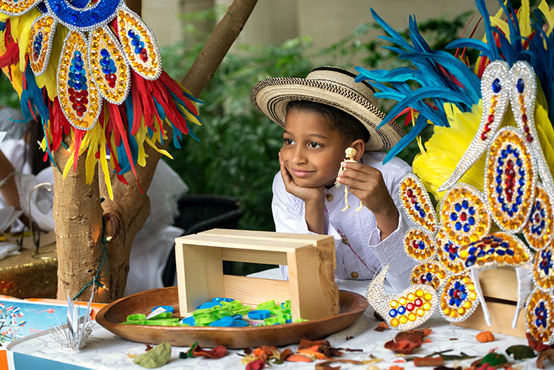 Seven-year-old Mario D'Agostino sits behind the Grupo Cultural Latinos En Rochester table during the Memorial Art Gallery's Hispanic/Latino Heritage Family Day Oct. 8.