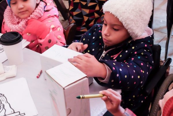 At Roc Holiday Village Dec. 28, children color boxes to be left under their beds for the Three Kings to fill.