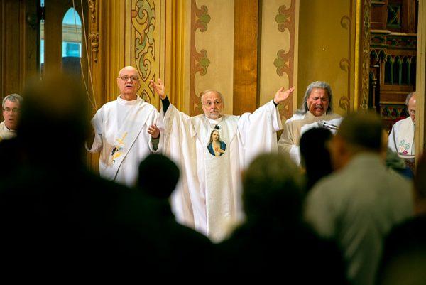 A priest raises his hands