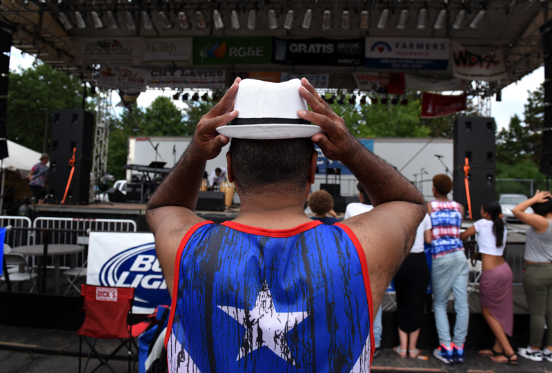 Man holds his hat while listening to musical acts.