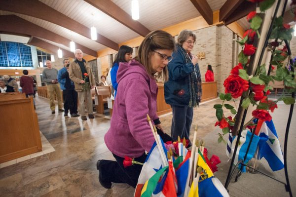 Woman kneels to place flowers in church.