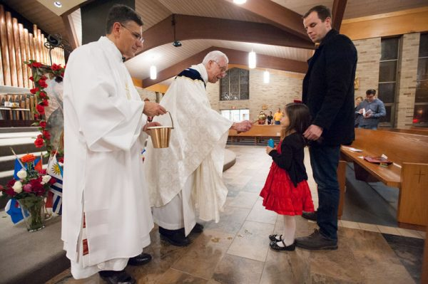 Priests bless girl in church.
