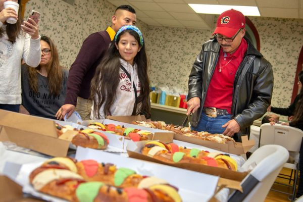 Victor Cortez cuts into a rosca de reyes, a pastry traditionally eaten to celebrate the Feast of the Epiphany.