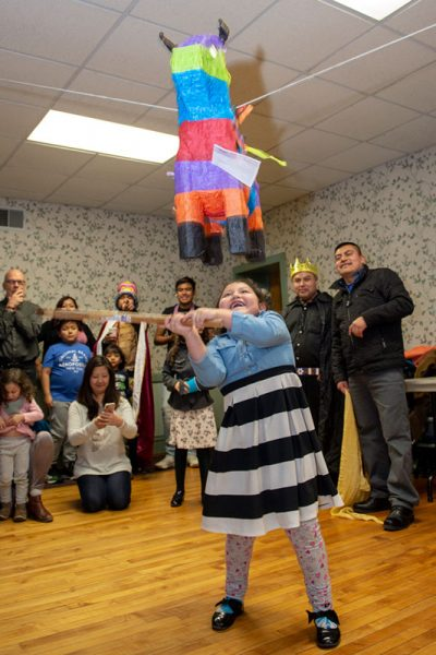 Arisbeth Aguilar hits the piñata during the celebration.