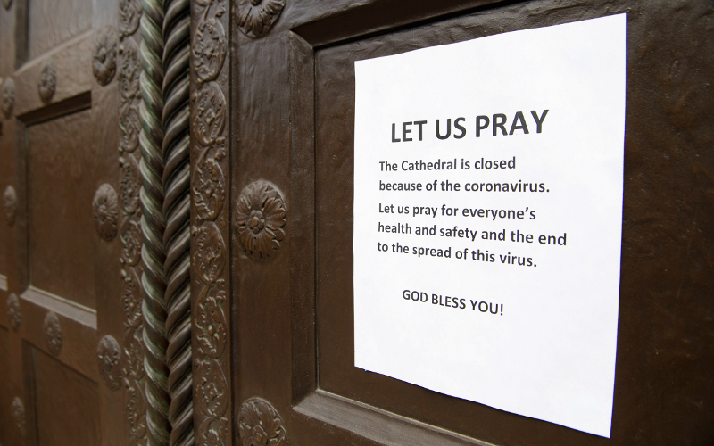 Sign on cathedral door says it is closed due to coronavirus