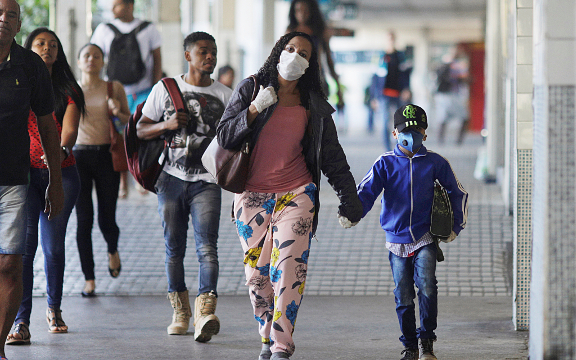 Woman and boy walk while wearing protective masks