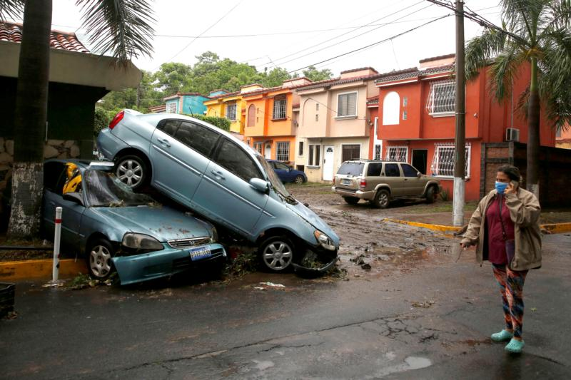 A woman wearing a protective mask walks past damaged cars in San Salvador, El Salvador, May 31, 2020, after Tropical Storm Amanda swept through the area. (CNS photo by Jose Cabezas/Reuters)