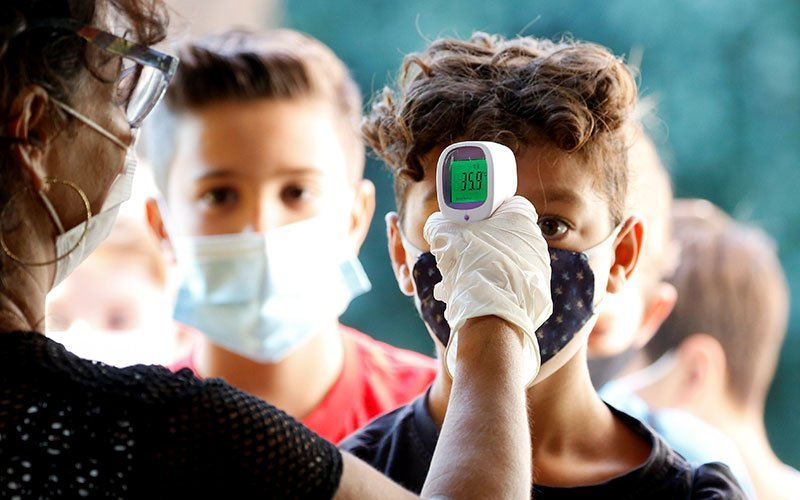 A boy has his temperature checked at Simonetta Salacone primary and secondary school in Rome Sept. 14, 2020, after students returned for the first time since March during the COVID-19 pandemic.