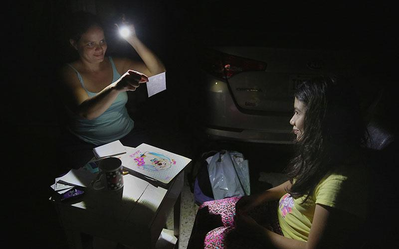 In this 2017 file photo, Margarita Rodriguez holds a flashlight as she quizzes her 11-year-old daughter Isel Martinez on homework outside their home in San Juan, Puerto Rico.