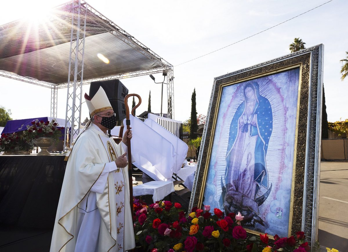 Archbishop José H. Gomez of Los Angeles pays tribute to a portrait of Our Lady of Guadalupe during the 89th procession and Mass Dec. 6, 2020, at the Mission San Gabriel in Los Angeles honoring St. Juan Diego and Our Lady of Guadalupe, whose feast day is Dec. 12. (CNS photo/Victor Aleman, Angelus)