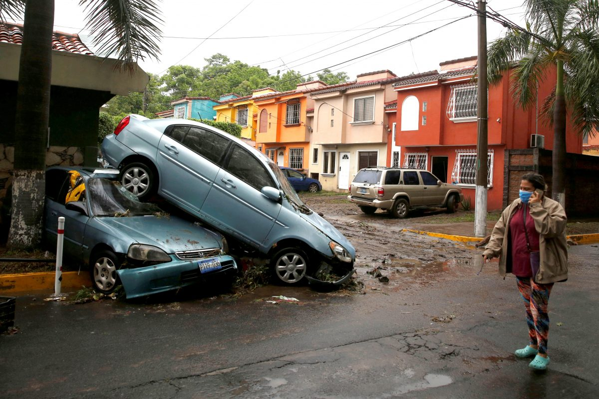 A woman wearing a protective mask walks past damaged cars in San Salvador, El Salvador, May 31, 2020, after Tropical Storm Amanda swept through the area.