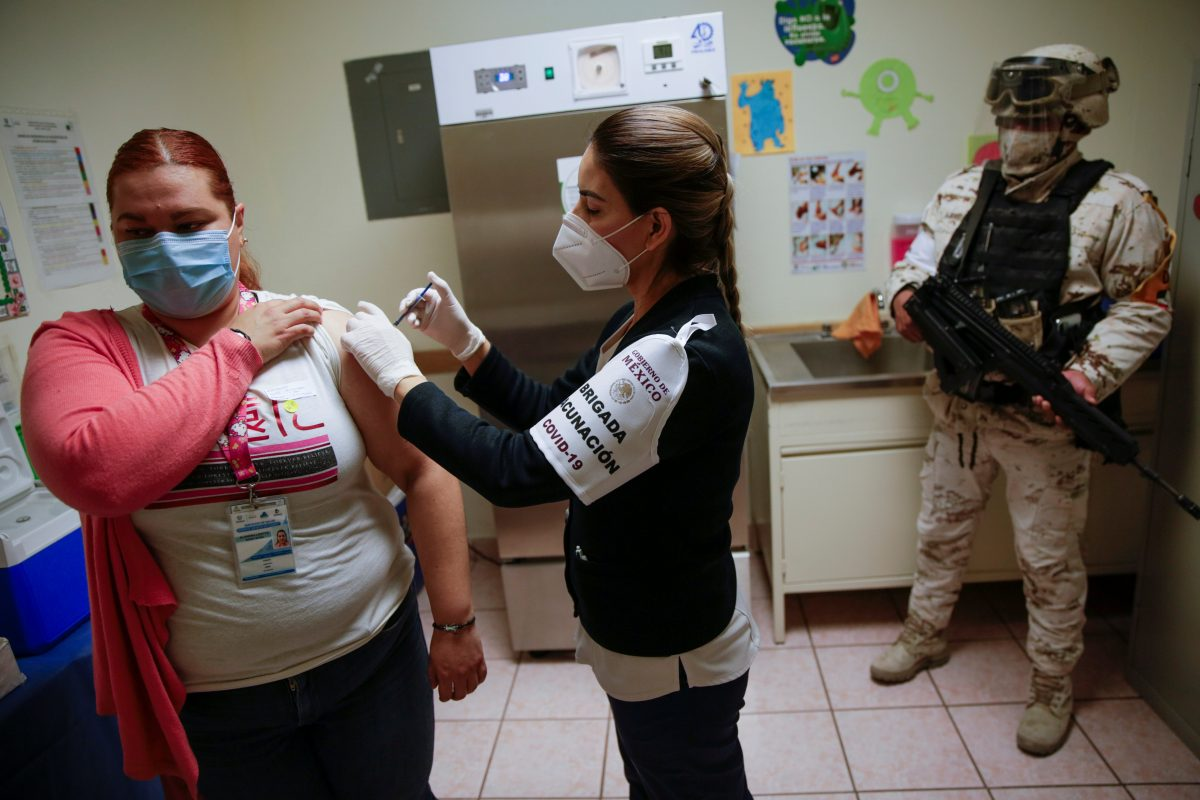 A health care worker receives an injection with a dose of the Pfizer-BioNTech COVID-19 vaccine at a hospital in Ciudad Juarez, Mexico, Jan. 14, 2021.