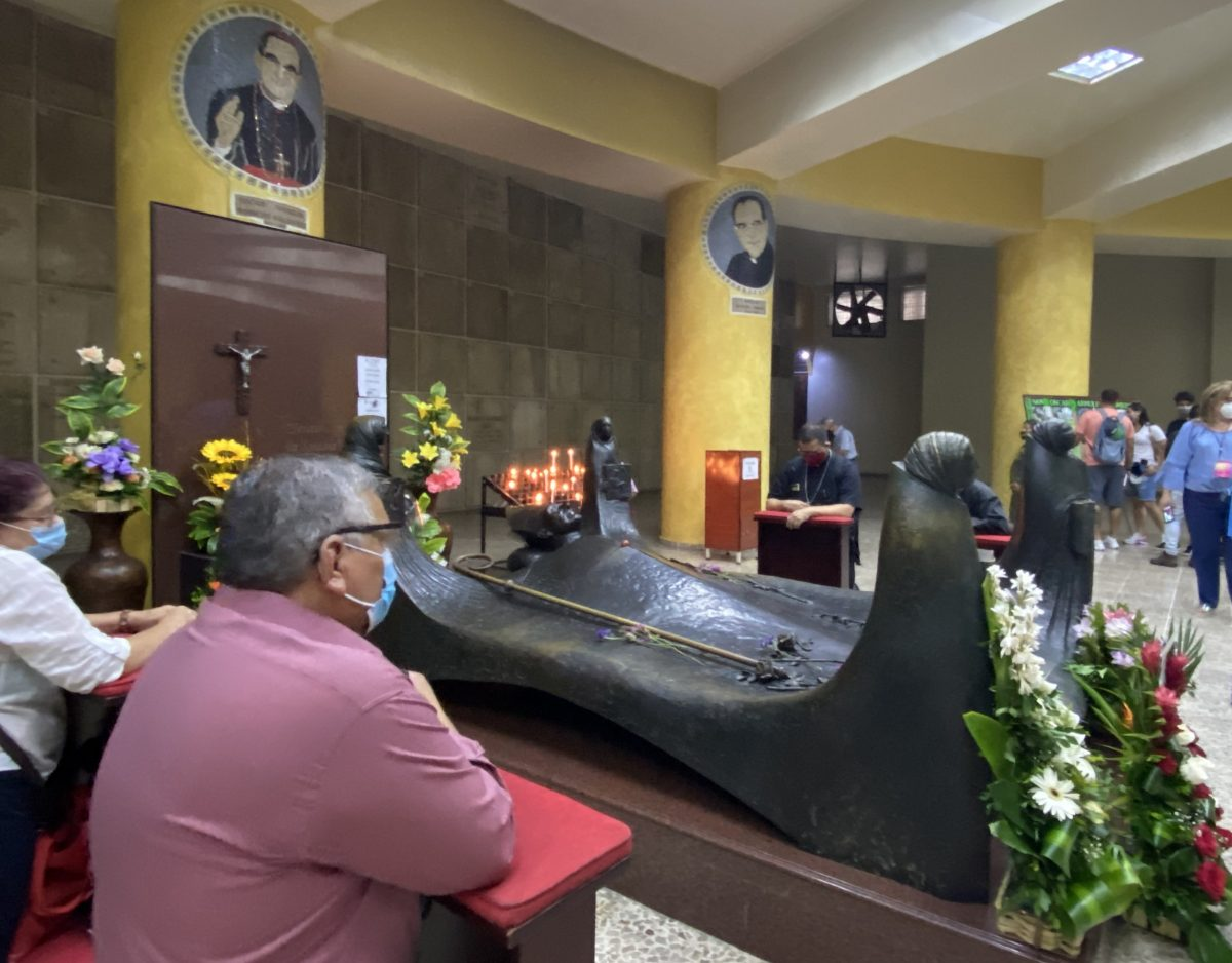With COVID-19 restrictions in place, lay Catholics gather in smaller groups around the tomb of St. Oscar Romero at the cathedral in San Salvador, EL Salvador, March 24, 2021, the 41st anniversary of the Salvadoran saint's martyrdom.