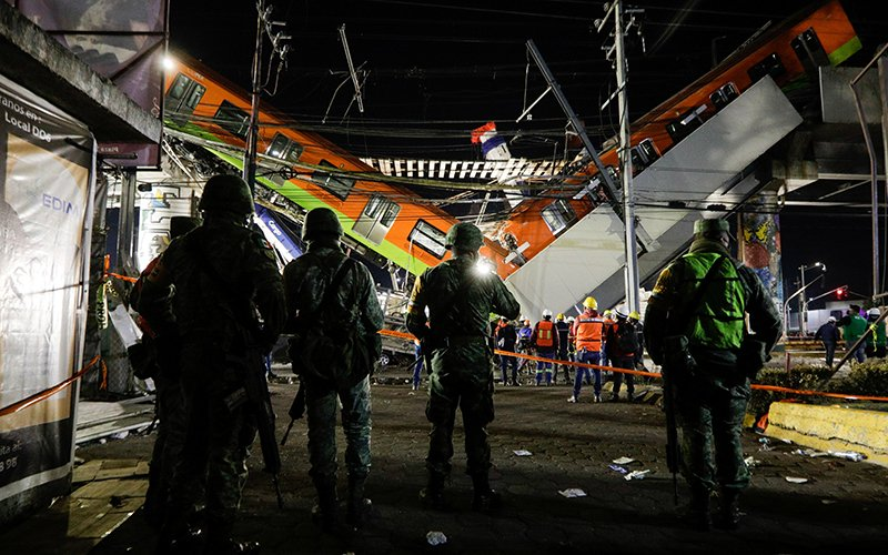 Soldiers stand as rescuers work at a site where an overpass for a metro partially collapsed May 3, 2021, with train cars on it at Olivos station in Mexico City. Picture taken May 4, 2021.
