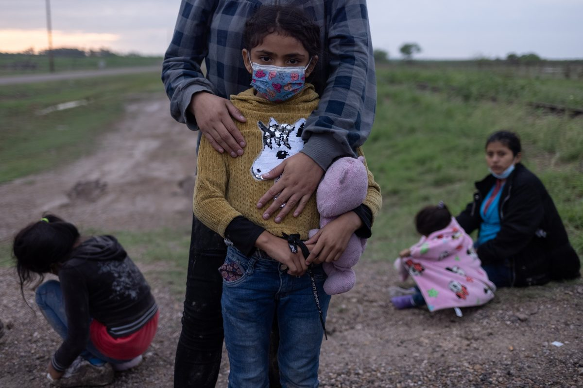 A migrant family from Honduras seeking asylum in the U.S. waits to be transported to a Border Patrol processing facility after crossing the Rio Grande into La Joya, Texas, May 13, 2021.