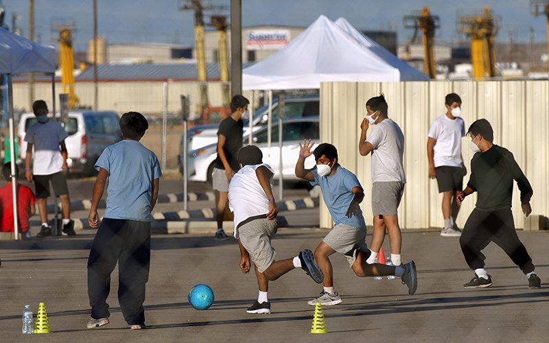 Unaccompanied child migrants play soccer at a temporary housing facility in Midland, Texas, April 8, 2021. (