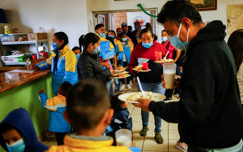 Migrants who were returned to Mexico under Title 42 after seeking asylum in the U.S., receive food during a quinceañera celebration at the Casa del Migrante shelter in Ciudad Juarez, Mexico, Sept. 30, 2021.