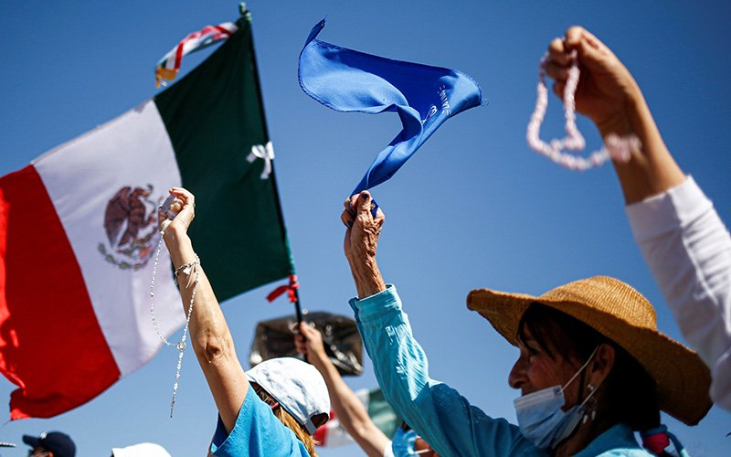 Protesters wave a Mexican flag, rosaries and a blue bandanna as people take part in a pro-life march in Mexico City Oct. 3, 2021, protesting the Mexican Supreme Court decision to decriminalize abortion.