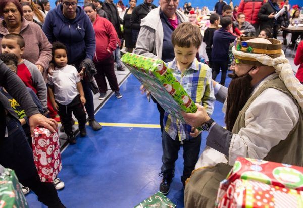 03 Children receive gifts from the Three Kings during the Bilingual Education Council's Three Kings celebration.