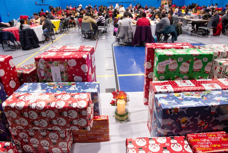 People eat and wait for gifts to be given out by the Three Kings Jan. 6 during the Rochester City School District Bilingual Education Council's Three King's celebration at Rochester's David F. Gantt R-Center.
