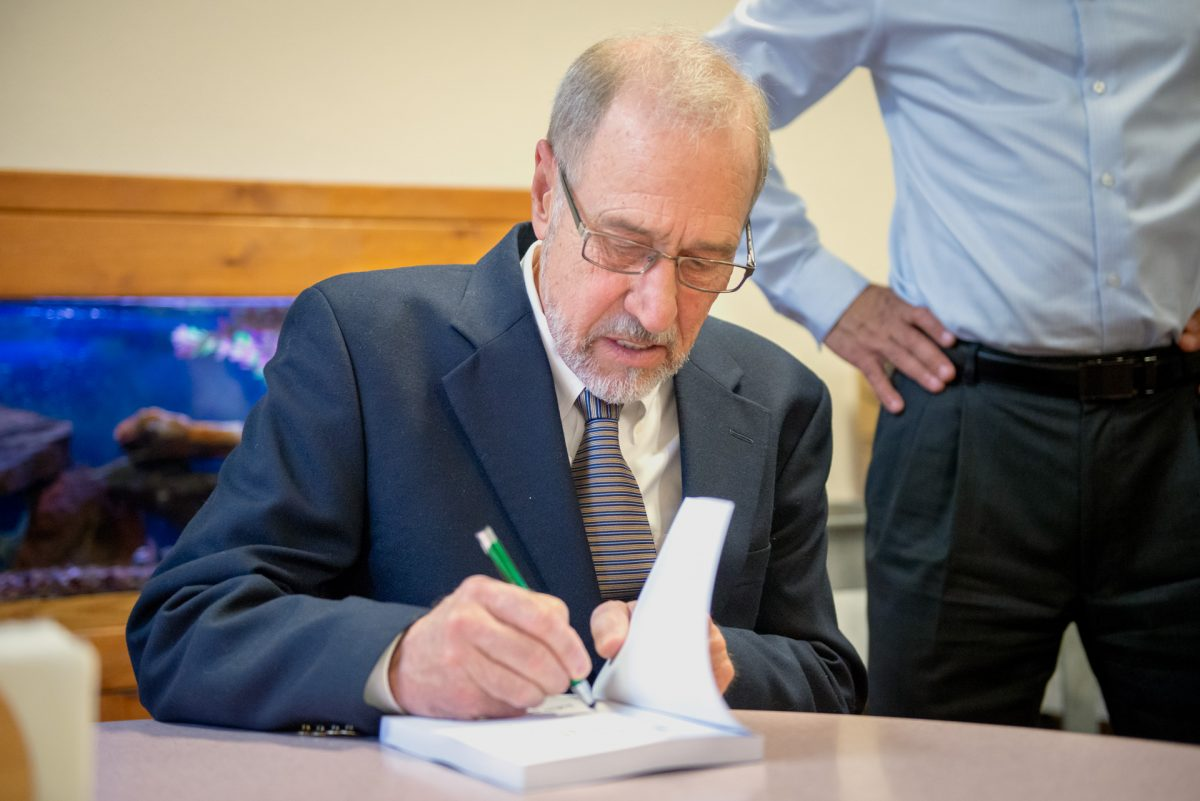 "Local author John Strazzabosco signs a copy of his book ""Ninety Feet Under: What Poverty Does to People"" during a June 14 launch event at the Mercy Center in Rochester."