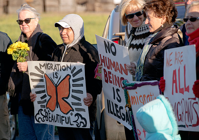 "Eliceo Sanchez holds a sign saying ""Migration is beautiful"" alongside other immigration rights advocates outside the New York State Police barracks in Williamson Nov. 2. The group delivered a letter asking the State Police to stop immigration status checks."