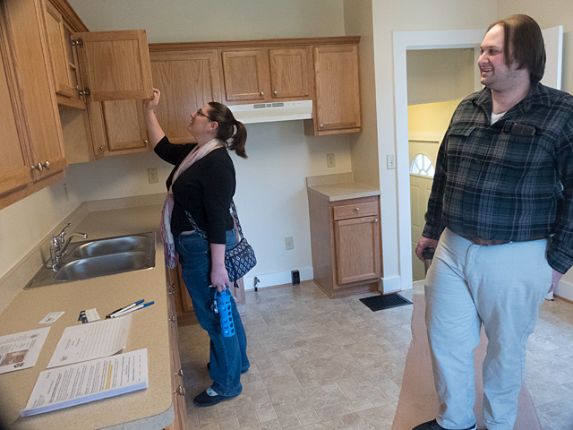 Lindsey and Chris Eklund look at the kitchen as they tour the 93 Wilmington Street house during an open house on April 2.in Rochester. Catholic Courier Photo by John Haeger