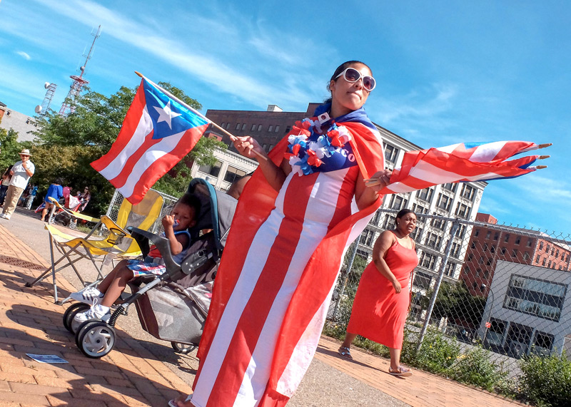 Yadelig Lopez watches the annual PR Festival Parade in Rochester  on July 29. El Mensajero Photo by John Haeger