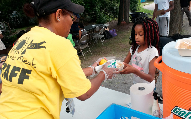 Silvia Mitchell serves meals at Conkey Corner Park on Aug 1 in Rochester. The ÒSummer Meals on WheelsÓ program drives healthy meals into neighborhoods without a nearby Summer Meals site Ð ensuring children arenÕt missing meals while school is out. EMC Photo by JOHN HAEGER