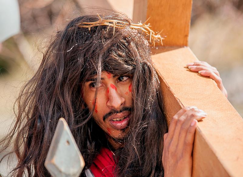 Man dressed as Jesus carries cross.