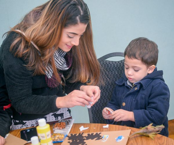Woman and child do crafts.
