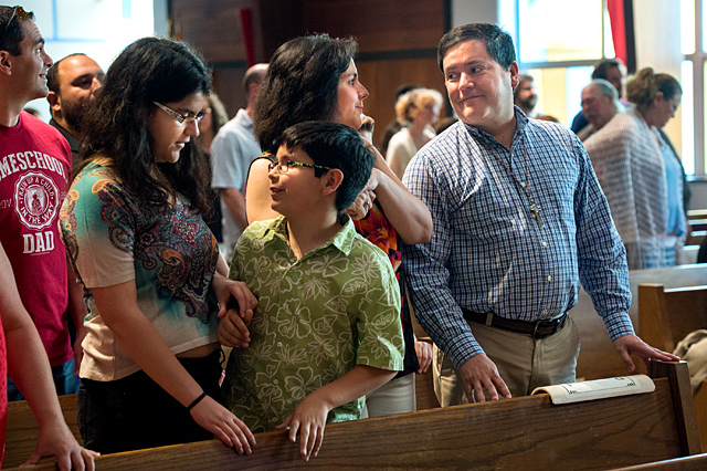 Members of the Rivera family, from left, Victoria, 18, Antonio, 10, Rita, and José offer each other a sign of peace during a May 28 Mass at St. Leo Church in Hilton.