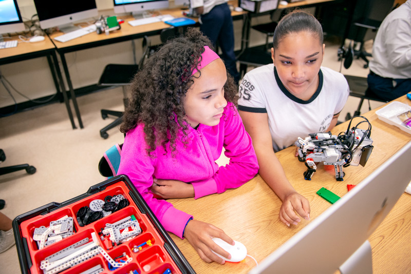 Sixth-graders Javiellys Pomales (left) and Destiny Pizarro make changes to the software on the robot dog they built in the extended learning program at Rochester School #9 focused on robotics June 13.